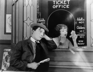 1924: American comedian Buster Keaton (1895-1966) standing outside the box office clutching his dollar bill while Ruth Holly applies her make-up in the film 'Sherlock Junior'.